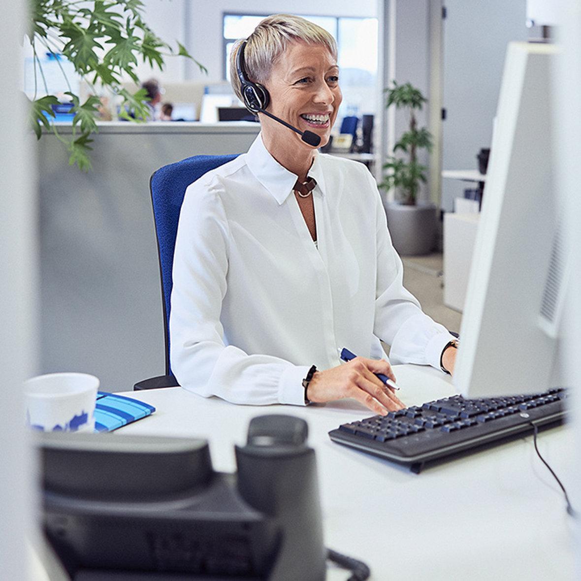 Telefonierende Frau mit Headset an Computer