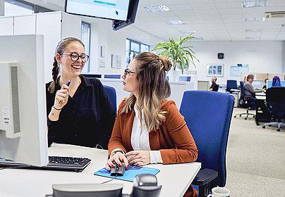 Zwei Frauen am Computer, die sich angeregt unterhalten