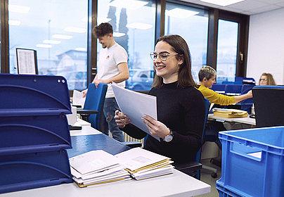 Frau, lächelnd, sortiert Dokumente in Ablage